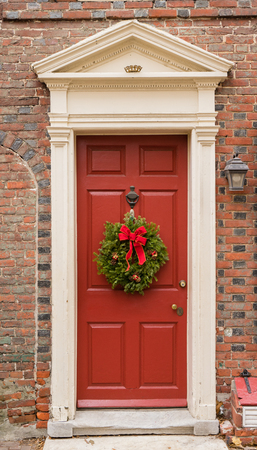 pediment: Colonial red doorway in historic Elfreths Alley in Philadelphia with pediment and  christmas wreath.