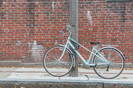 locked up: Bicycle locked up to a concrete post next to a briack wall. Stock Photo