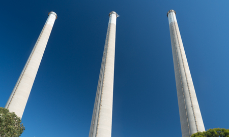 Industrial factory smoke stacks against a blue sky Stock Photo