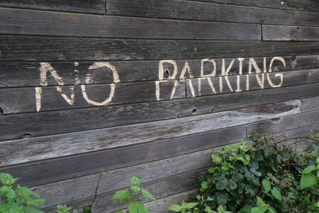 old sign: No parking sign on old wooden building