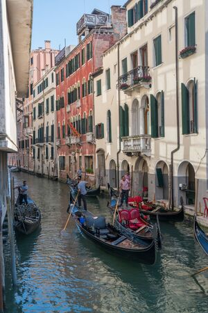navigate: VENICE, ITALY - JULY 1, 2016: Gondoliers navigate gondolas through a canal in Venice, Italy.