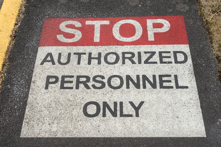 Stop Authorized Personnel Sign painted on sidewalk