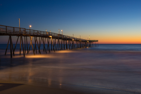 Sunrise long exposure of fishing pier along the beach of the Outer Banks of North Carolina Stock Photo