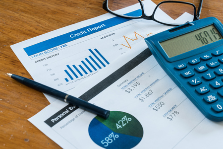 borrowing: Credit score report on desk with budget, calculator, pen and glasses Stock Photo