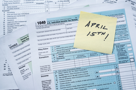 Collection of IRS federal income tax forms with reminder note of April 15th Stock Photo