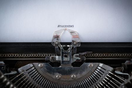 The hashtag #FakeNews typed on an old Typewriter 版權商用圖片