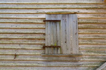 Old weathered wood barn window background on building