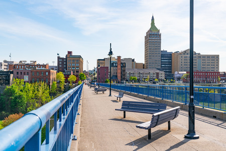 ROCHESTER, NY - MAY 14, 2018: Skyline of Rochester, New York along the Pont De Rennes Pedestrian Bridge which is part of the Genesee Riverway Trail