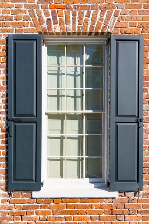 Exterior window of colonial brick home with black shutters