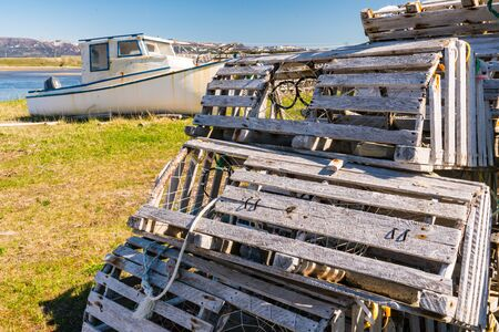 Old wooden lobster traps and fishing boats in Newfoundland, Canada
