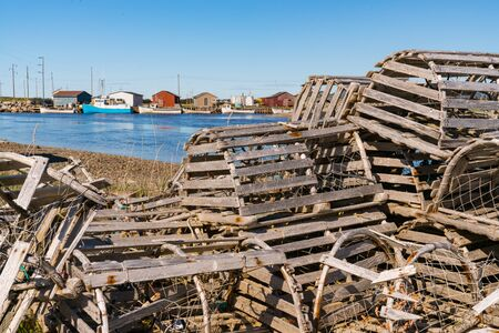Old wooden lobster traps and fishing boats in a fishing village in Newfoundland, Canada Stock fotó