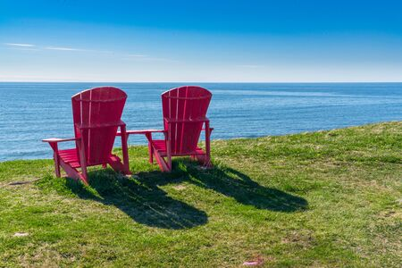 Two red adirondack chairs overlooking the ocean on the coast of Newfoundland in Gros Morne National Park, Canada