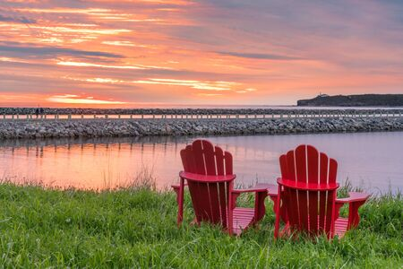 Red adirondack chairs along the ocean during sunset In Rocky Harbour,  Newfoundland, Canada