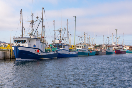 Twillingate, Newfoundland - June 13, 2019: Fishing boats lined up along the dock in the harbor of Twillingate, Newfoundland, Canada Sajtókép