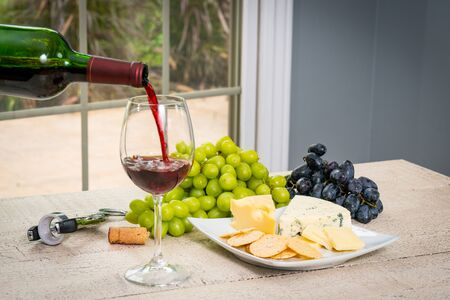 Glass of red wine with wine bottle, cheese, crackers, ham, almonds and grapes Standard-Bild