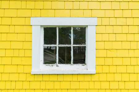 Old wood frame window with bright yellow clapboard siding