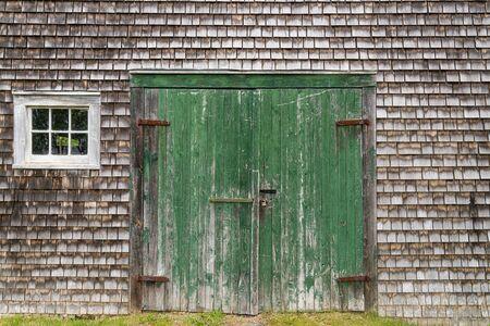 Weathered rustic old green barn doors with cedar shingles