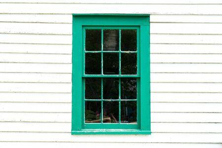 Old rustic green window frame on cedar shingles with weathered peeling