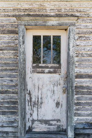 Old weathered white door with peeling paint on the front of abandoned house