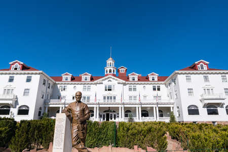 Estes Park, CO - October 31, 2020: Exterior of the historic Staley Hotel in Estes Park near Rocky Mountain National Park with statue of F. E. Stanley in the foreground.