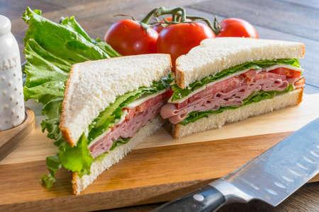 Fresh ham, tomato and cheese sandwich on cutting board