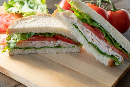 Fresh turkey, lettuce and tomato sandwich cut in half on cutting board Imagens