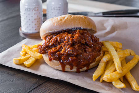 Pork barbecue sandwich with french-fried potatoes on brown paper