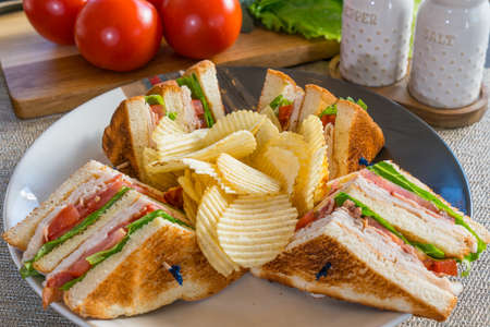 Fresh turkey club sandwich on white toast with potato chips on a plate Imagens