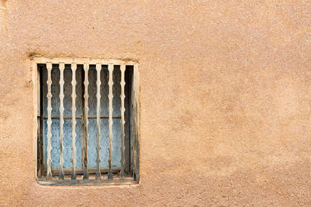 Old Southwestern Brown Adobe Wall and Window with decorative wooden spindles 免版税图像
