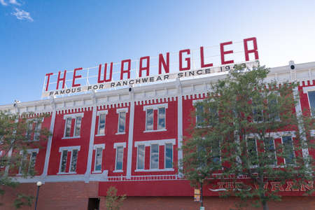 CHEYENNE, Wyoming - APRIL 27, 2018: Sign on top of The Wrangler in historic downtown Cheyenne Wyoming. The three story red-painted brick building dominates a corner of Capitol Avenue and Lincolnway.