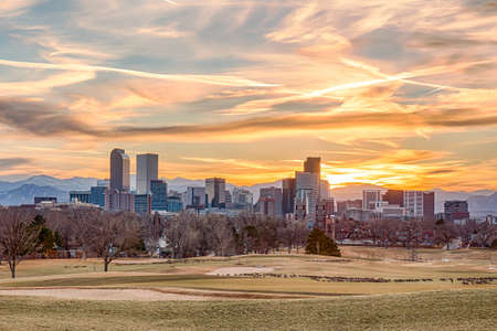 Denver, Colorado city skyline at sunset with the Rocky Mountains in the background