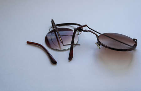 damaged dark sunglasses with round lenses. Sunglasses that sat on when they were in the back pocket of his jeans.