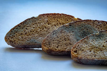 three pieces of spoiled rye bread covered with white and black mold