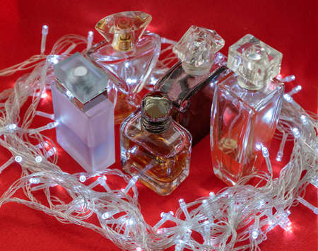 Different shape and color of the bottles of perfume on a red background. 免版税图像