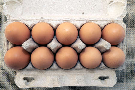 Chicken brown fresh raw eggs in an egg container. Ingredients for cooking. Healthy eating is a concept Stock Photo