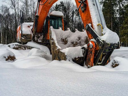 Large yellow excavator on the background of a winter landscape