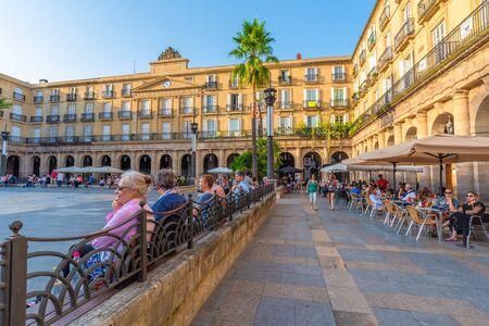 16/09-19, Bilbao, Spanje. Mensen en kinderen genieten van de middag op Plaza Nueva. De Koninklijke Academie van de Baskische taal in het midden van de foto