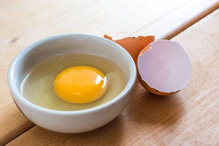 eggshell: Egg Yolk In White Bowl And Eggshell On Wood Table