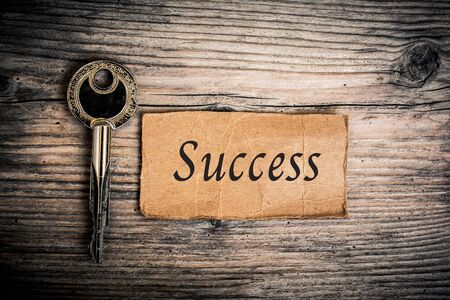 Key and Text Success  On Wood Background