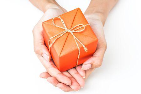 Two Hand Holding Orange Gift Box on White Background