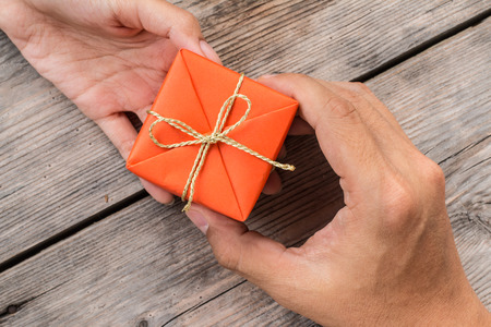 Hand Giving Orange Gift Box and Yellow Ribbon on Wood Background
