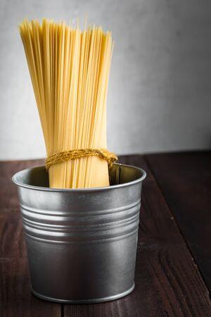 table wood: spaghetti uncooked in bucket on wood table Stockfoto