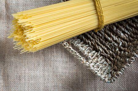 gunny: spaghetti uncooked in basket on gunny