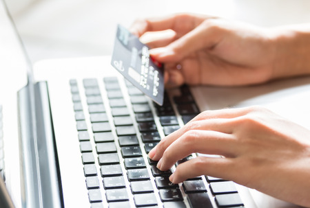 Young woman holding a credit card and typing. Online shopping on the internet using a laptop Archivio Fotografico
