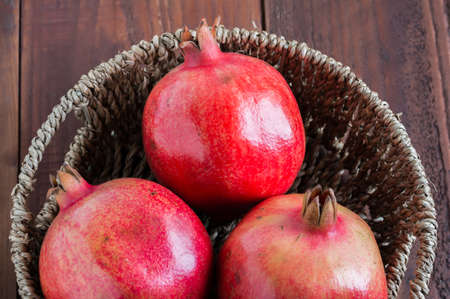 pomegranate in basket on wood table photo