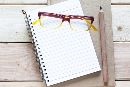 notebook  pencil and eyeglasses  on wood table photo