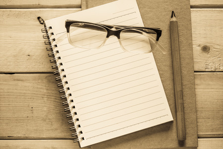 notebook  pencil and eyeglasses  on wood table  antique style photo