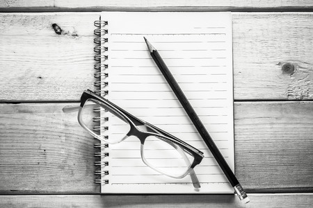 notebook  pencil and eyeglasses  on wood table  black and white style photo