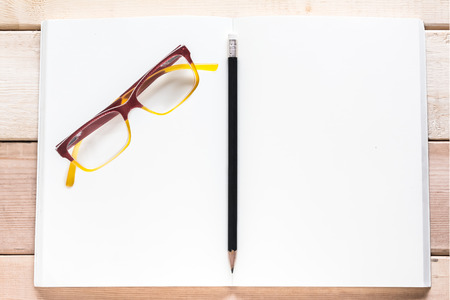 open notebook  pencil and eyeglasses on wood table photo