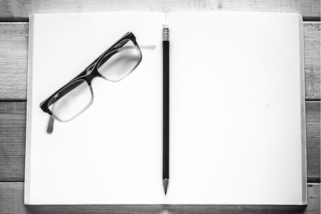 open notebook  pencil and eyeglasses on wood table  black and white style photo